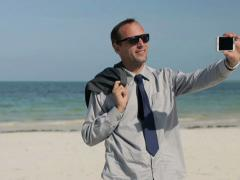 Businessman taking selfie with smartphone on exotic beach NTSC Stock Footage