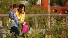 Woman teaching daughter how to water plants in an urban garden Stock Footage