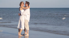 Caucasian couple hugging on beach with birds Stock Footage