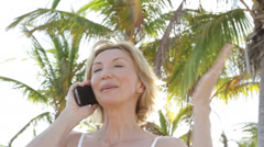 Close up of Caucasian woman under palm trees on cell phone - stock footage