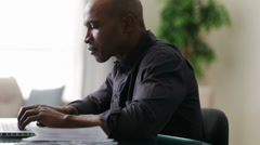 Black man sitting at table using laptop - stock footage