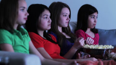 Four girls on sofa eating popcorn watching funny movie Stock Footage