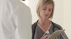Caucasian make and female doctors talking with digital tablet Stock Footage