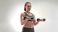 Athletic caucasian woman curling weights both at one time - stock footage