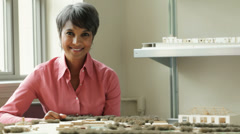Stock Video Footage of Mixed race businesswoman in office with architectural models