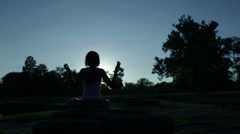 Silhouette of sitting black woman doing yoga Stock Footage