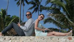 Happy business couple with tablet and laptop in exotic location HD Stock Footage