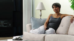 Mixed race woman wearing pajamas on sofa watching television - stock footage