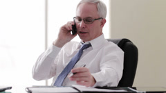 Older caucasian businessman at desk talking on cell phone Stock Footage