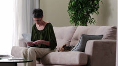Older upset caucasian woman reading paperwork on sofa with dog Stock Footage