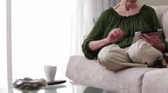 Older caucasian woman with dog drinking coffee on sofa using digital tablet Stock Footage