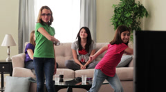 Girls playing tennis video game with girls on sofa in background - stock footage