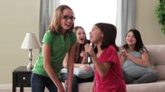 Tytöt leikkivät laulaa karaokea tyttöjen sohvalla taustalla Arkistovideo
