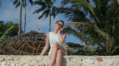 Beautiful businesswoman talking on cellphone in exotic location HD Stock Footage