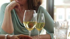 Two caucasian women drinking wine and laughing - stock footage