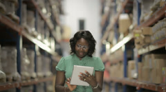 Black woman in warehouse using digital tablet Stock Footage