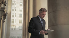 Caucasian businessman standing near pillar using digital tablet Stock Footage