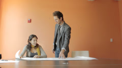 Businessman and businesswoman at table discussing blueprint Stock Footage