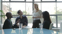 Business people talking in meeting near window Stock Footage