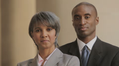 Businesswoman and businessman looking at camera Stock Footage