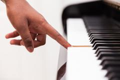 African american hand playing piano - touching piano keys - black people Stock Photos