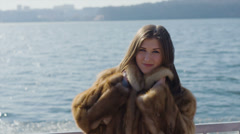 Beautiful young girl outdoors in a fur vest 14-bit RAW Stock Footage