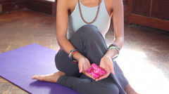 Mixed race yoga instructor holding flowers on exercise mat Stock Footage