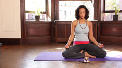 Mixed race yoga instructor sitting cross-legged on exercise mat - stock footage