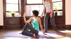 Female yoga instructor correcting the pose of student Stock Footage