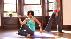 Female yoga instructor correcting the pose of student Stock Footage