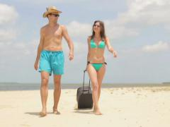 Couple with valise walking on beautiful exotic beach NTSC Stock Footage