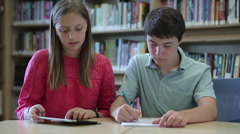Caucasian junior high students studying in library - stock footage