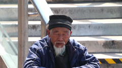 Old Chinese beggar sitting on stairs Stock Footage