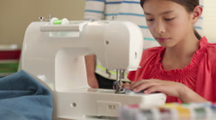 Mother and daughter using sewing machine Stock Footage