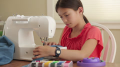 Mixed race girl using sewing machine Stock Footage