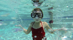 Caucasian girl with goggles swimming underwater Stock Footage