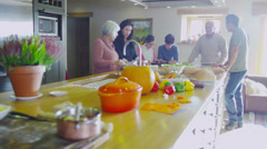 Three generations of happy family preparing a meal together at home Stock Footage