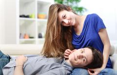 Cute man lengthened on the thighs of his girlfriend on a sofa Stock Photos