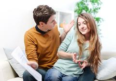 young anxious couple quarrels by consulting their bank account - stock photo