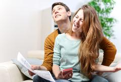 Happy young couple consulting their bank account with joy Stock Photos