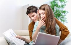 young anxious couple consults their bank account - stock photo