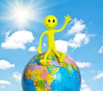 On top of the world - smilie sitting on the globe - stock photo