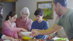Three generations of happy family preparing a meal together at home - stock footage