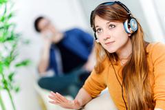 Beautiful blond listening to some music while her boyfriend is bored Stock Photos