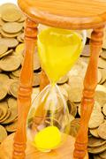 Stock Photo of Time is money concept - hourglass and coins