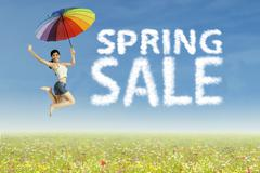 woman jumping with spring sale clouds - stock photo