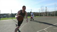 Basketball game with three guys and one slam dunking - stock footage