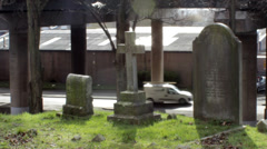 Static scene of mouldy tombstones and cross with a car traffic in the background Stock Footage