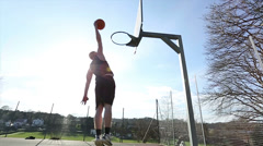 Basketball player slam dunking the ball Stock Footage