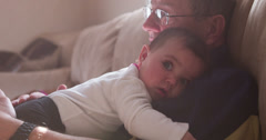 Granpa and baby laying on couch in sunshine pan 4k Stock Footage